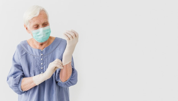 Front view of elder woman with medical mask and surgical gloves
