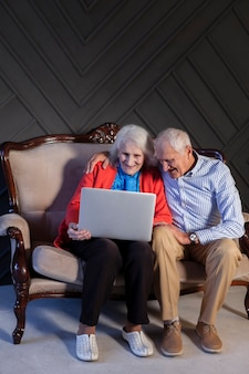 Front view elderly couple using a laptop