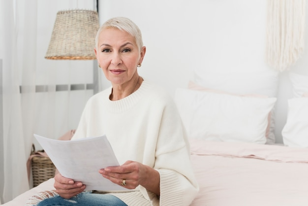 Front view of elderly woman in bed holding papers