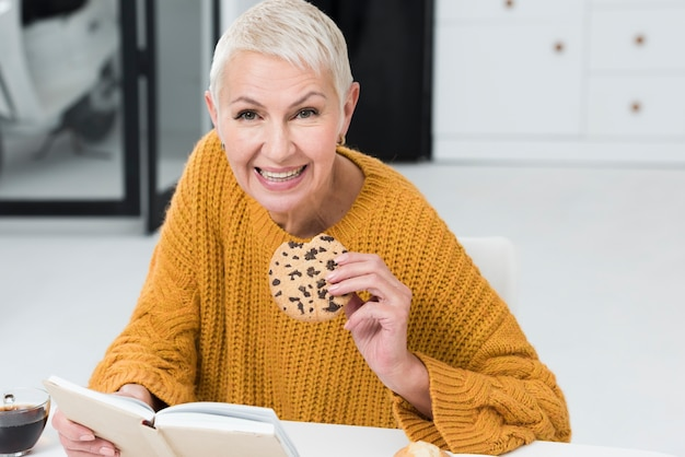 Front view of elderly woman holding big cookie and smiling