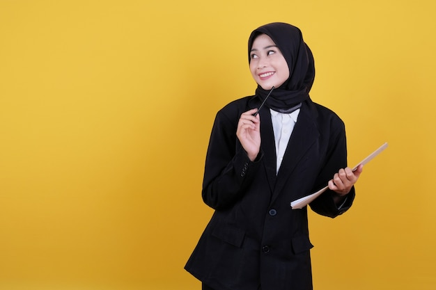 Front view of elegant businesswoman holding clipboard, getting new idea