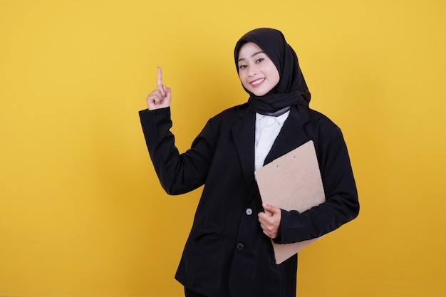 Front view of elegant businesswoman holding clipboard and pointing up