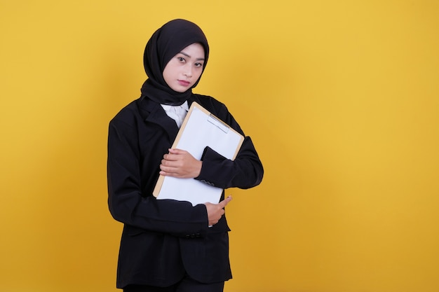 Front view of elegant businesswoman holding clipboard, satisfied female worker