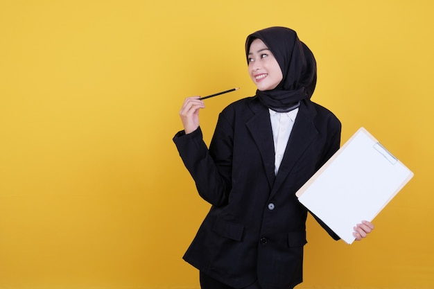 Front view of elegant businesswoman holding clipboard, thinking new idea