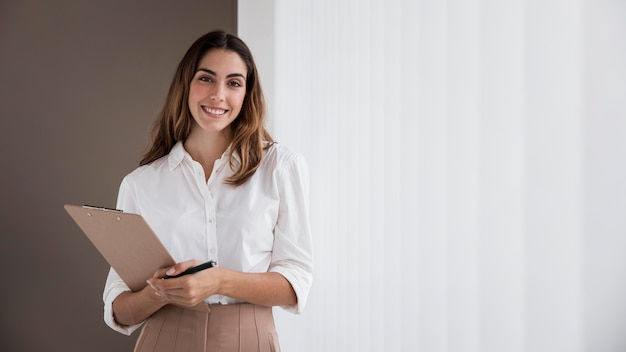 Front view of elegant businesswoman holding clipboard with copy space