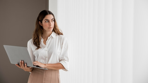 Front view of elegant businesswoman holding laptop with copy space