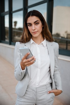 Front view of elegant businesswoman holding smartphone in the city