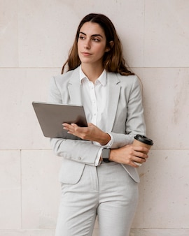 Front view of elegant businesswoman holding tablet and coffee cup