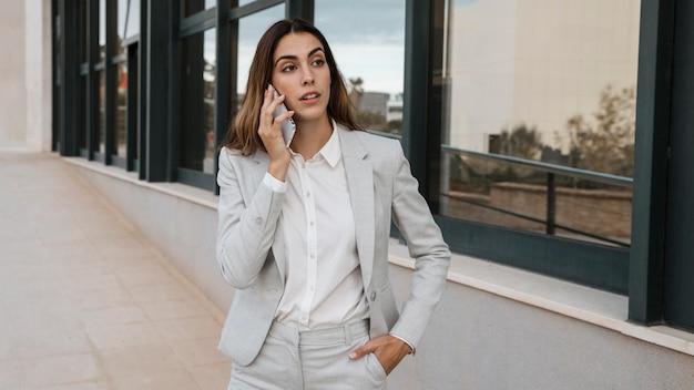 Vista frontale di elegante imprenditrice parlando al telefono in città