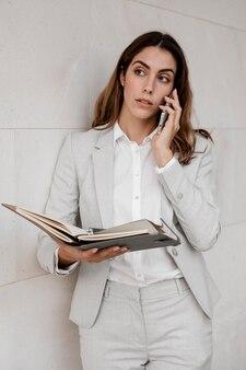 Vista frontale della donna di affari elegante con ordine del giorno parlando al telefono