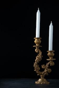 Vista frontale dell'elegante candelabro con candele bianche su oscurità