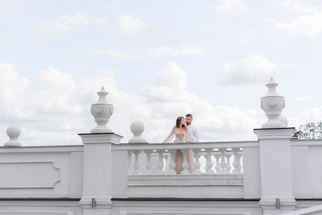 Front view of elegant newlyweds stand on a white bridge on a background of blue sky