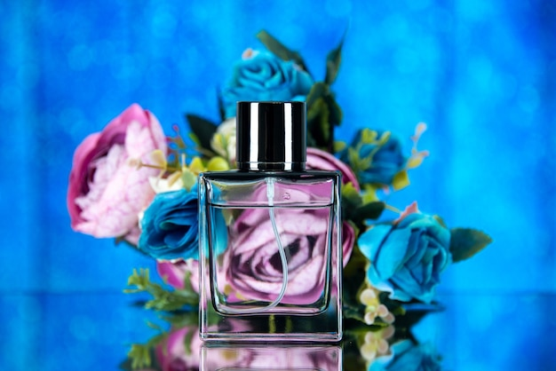 Front view elegant perfume bottle colored flowers on blue background