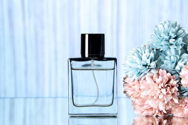 Elegante bottiglia di profumo vista frontale e fiori colorati su sfondo azzurro
