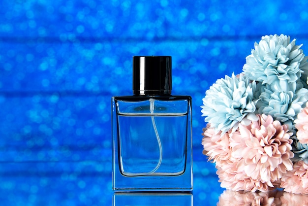 Front view of elegant perfume and colored flowers on blue background