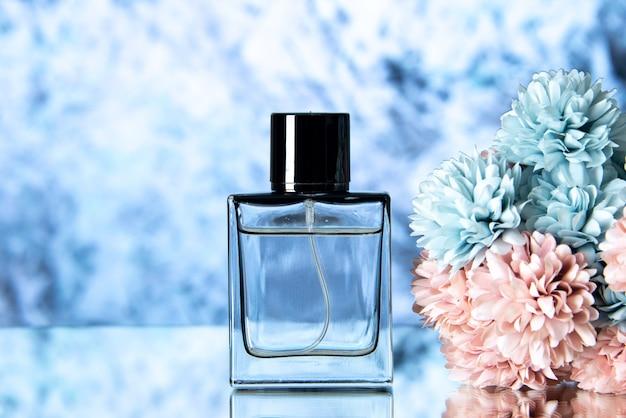 Vista frontale elegante profumo di fiori colorati su sfondo azzurro spazio libero