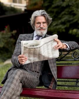 Front view elegant senior male reading newspaper