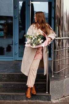 Vista frontale della donna elegante che tiene un mazzo di fiori all'aperto in città