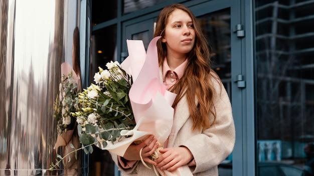 Vista frontale della donna elegante che tiene un mazzo di fiori all'aperto