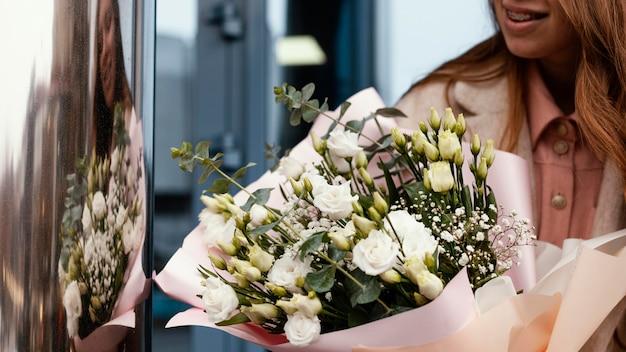 Vista frontale della donna elegante che tiene un mazzo di fiori all'esterno