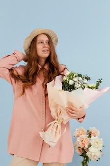 Vista frontale della donna elegante in posa con bouquet di fiori primaverili
