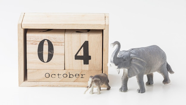 Front view of elephant figurines with wooden calendar for animal day