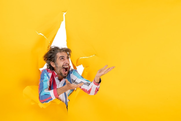 Front view of an emotional and crazy funny young guy looking up through a torn hole in yellow paper