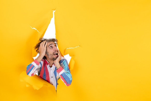 Front view of an emotional and crazy young guy looking up through a torn hole in yellow paper