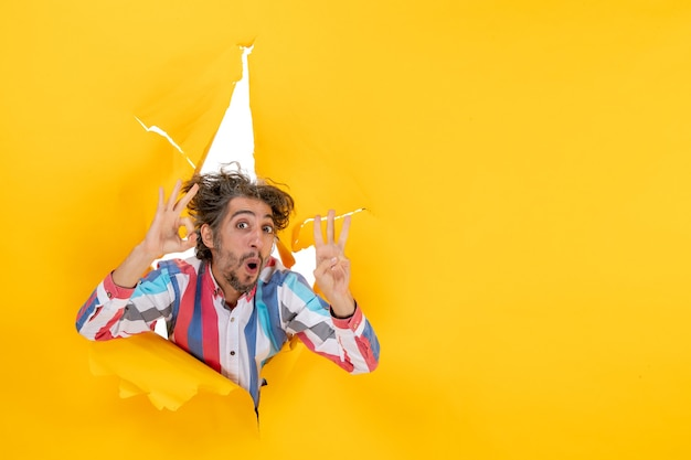 Vista frontale di un giovane ragazzo emotivo e pazzo che mostra tre attraverso un buco strappato in carta gialla