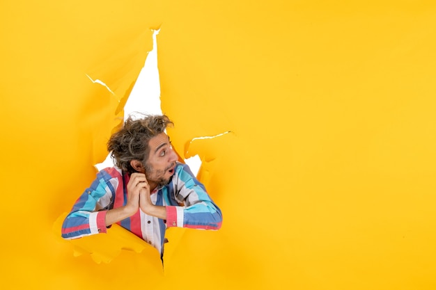 Vista frontale di un giovane ragazzo emotivo ed esausto concentrato su qualcosa attraverso un buco strappato in carta gialla