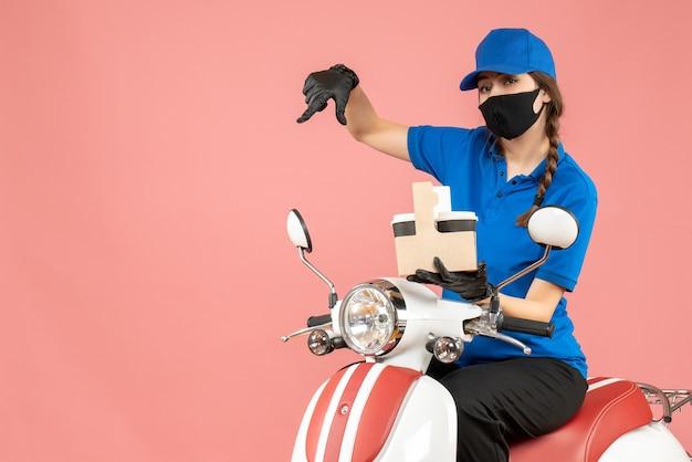 Vista frontale della persona di consegna femminile emotiva che indossa maschera medica e guanti seduto su scooter che consegna ordini su sfondo pesca pastello