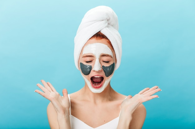 Front view of emotional girl screaming while doing skincare treatment. studio shot of amazing lady with face mask isolated on blue background.