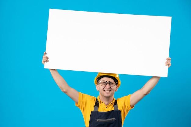 Эмоциональный мужчина-строитель в униформе с бумажным планом на синем, вид спереди