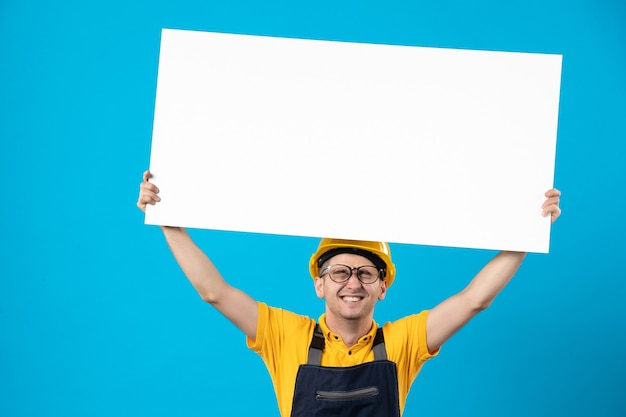 Front view emotional male builder in uniform with paper plan on blue