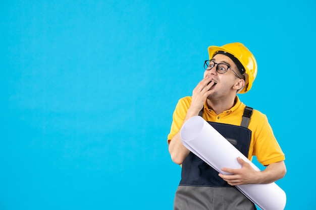 Front view of emotional male builder in yellow uniform with plan blue wall