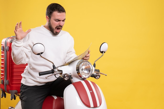 Front view of emotional man sitting on motorcycle with suitcase on it holding map on isolated yellow background