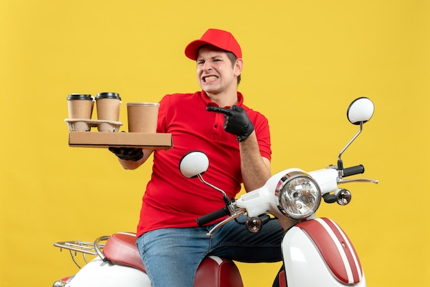 Vista frontale dell'uomo di corriere nervoso emotivo che indossa guanti di camicetta e cappello rossi nella mascherina medica che consegna l'ordine che si siede sugli ordini della tenuta dello scooter