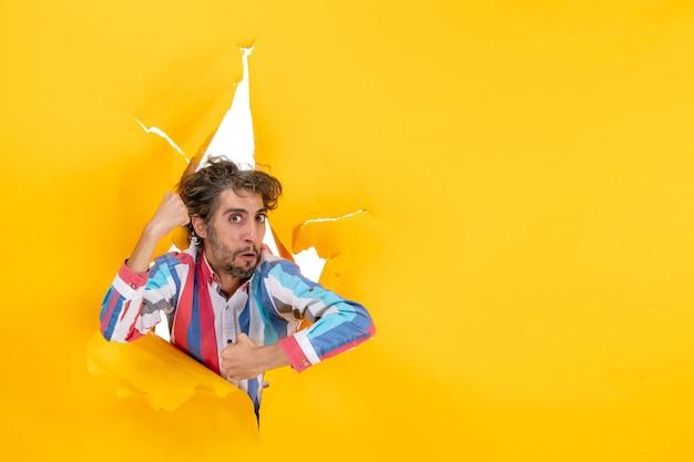 Vista frontale di un giovane ragazzo emotivo e nervoso che posa per la macchina fotografica attraverso un buco strappato in carta gialla