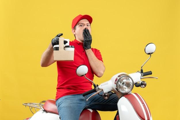 Vista frontale dell'uomo di corriere scioccato emotivo che indossa guanti di camicetta e cappello rossi in mascherina medica che consegna ordine seduto su scooter tenendo gli ordini