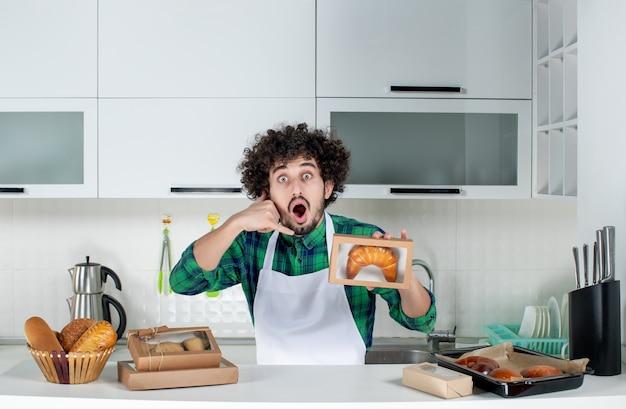 Vista frontale di un uomo emotivamente sorpreso che mostra la pasticceria appena sfornata in una piccola scatola e mi fa un gesto di chiamata nella cucina bianca