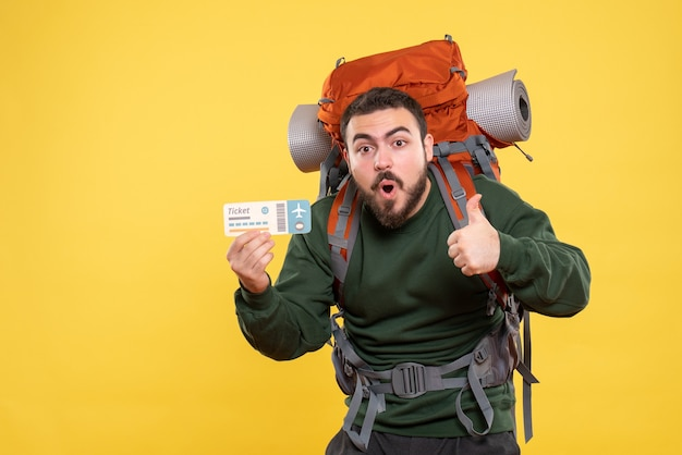 Front view of emotional surprised travelling guy with backpack and holding ticket making ok gesture on yellow background