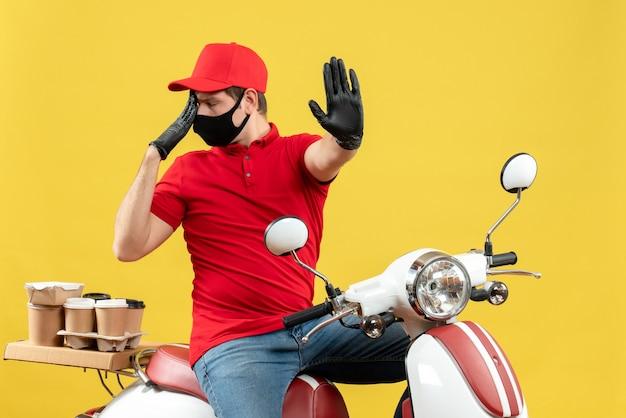 Vista frontale del giovane adulto emotivo che indossa guanti rossi della camicetta e del cappello nella mascherina medica che trasporta l'ordine che si siede sul motorino su fondo giallo