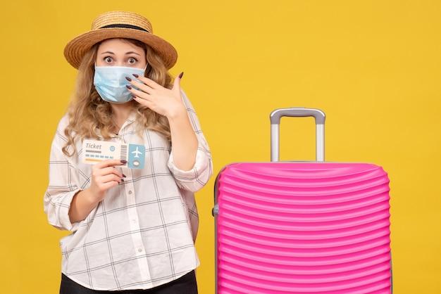 Vista frontale della giovane donna emotiva che indossa la maschera che mostra il biglietto e in piedi vicino alla sua borsa rosa