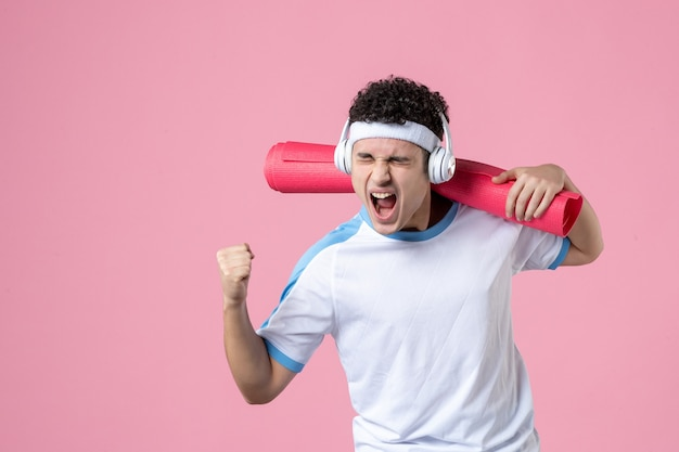 Front view emotional young male in sport clothes with yoga mat