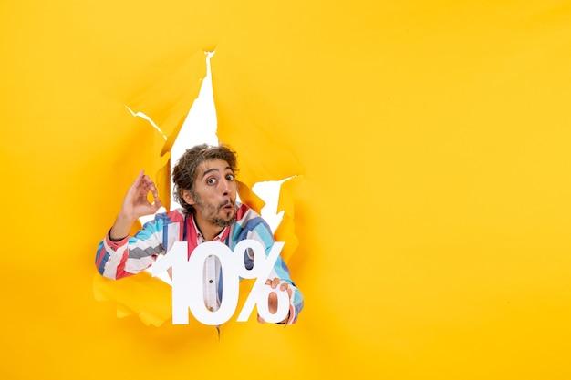 Vista frontale di un giovane emotivo che mostra il dieci percento e punta verso l'alto in un buco strappato in carta gialla