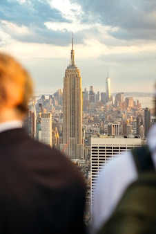 Front view of empire state building in manhattan, new york city, between two unrecognizable men in foreground