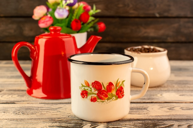 Front view of empty cup with red kettle brown coffee seeds and flowers on the wooden desk