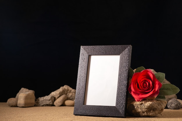 Front view of empty picture frame with different stones on dark
