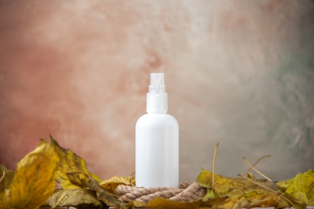 Front view empty spray bottle around fall leaves on nude background