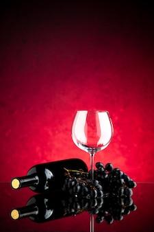 Bicchiere da vino vuoto vista frontale con uva scura sullo sfondo rosa